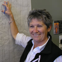 Smiling woman with her hand on a mural-sized pencil drawing on a wall
