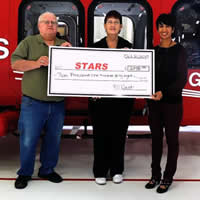 Duane and Linda Pilson present STARS foundation executive, Nafisa Taimuri with a cheque for over $2100