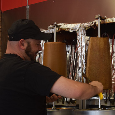 Sal Salame, owner of Rocky's Donair Cranbrook, slicing beef for a Donair.