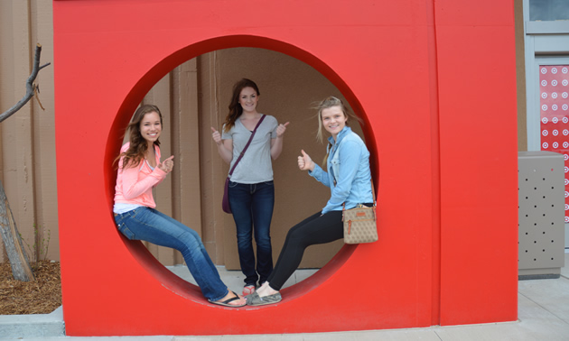 Three teenage girls within a circular cutout in a red-coloured upright square