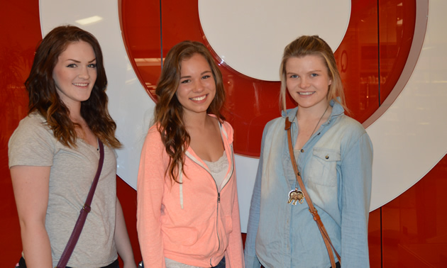 Three teenage girls stand in front of a red-on-white target