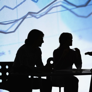 A silhouette of 3 people in a business meeting with an upward graph in the background.