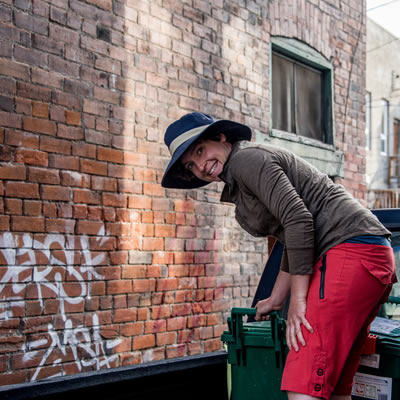 Ashley Taylor is leaning over a green bin that she collects food waste in.