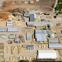 Aerial view of a large lumber yard, including industrial buildings