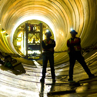 Two workers are silhouetted against a yellow lit tunnel.
