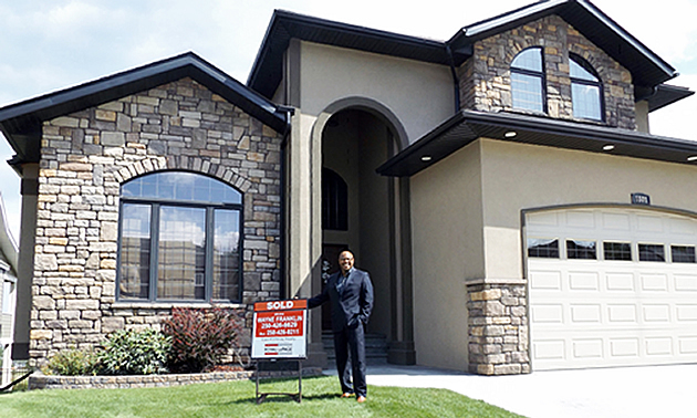 Wayne Franklin holding on to a for sale sign outside a large brick home.