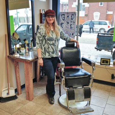 Becky Winchester stands beside a chair, ready to cut your hair