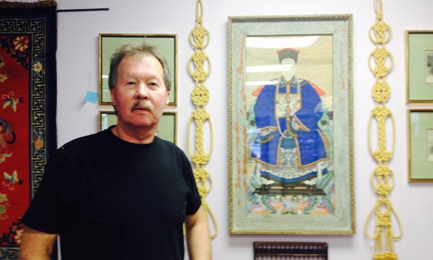Don Langvand, owner of Atlantis Antiques in Marysville, is standing beside a very old painting of an emperor executed on parchment.