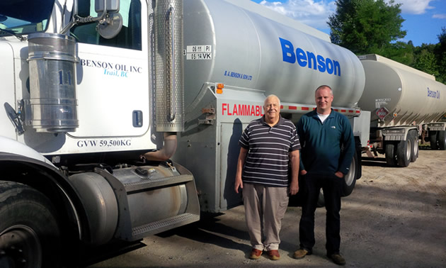 Two men standing beside a fuel truck.