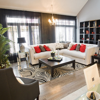 A living room with a white corner sofa, black book shelf and coffee table, and red cushions and accessories