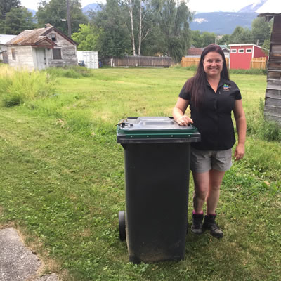 Sarah Osadetz, WildSafeBC community co-ordinator for Golden, is standing next to a bear-resistant garbage bin.