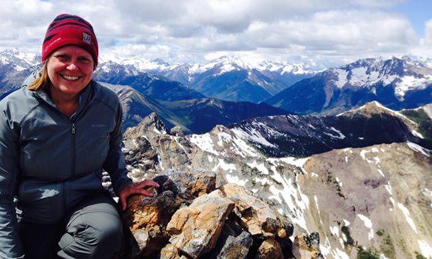 The author is sitting on top of Mount Brewer near Invermere with a sea of mountains in the background.