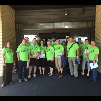 Group of Business Walk members, dressed in bright green t-shirts, heading out to local businesses.
