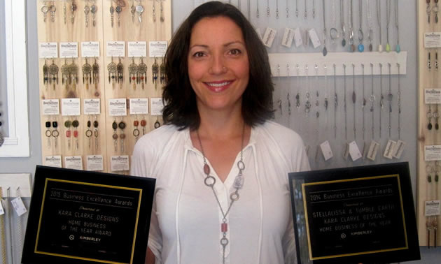 Custom jeweler Kara Clarke has won several chamber awards from the Kimberley Chamber of Commerce including Home Business of the Year. She stands in front of a wall full of hanging necklaces.