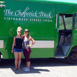 Sydney and Taylor Salvador are standing in front of their Chopsticks Truck.