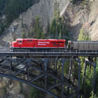Photo of a coal train driving across a large bridge in the mountains.
