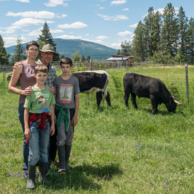 The Bolter family (parents and two kids) stand in a pasture with their beef cows in the background.