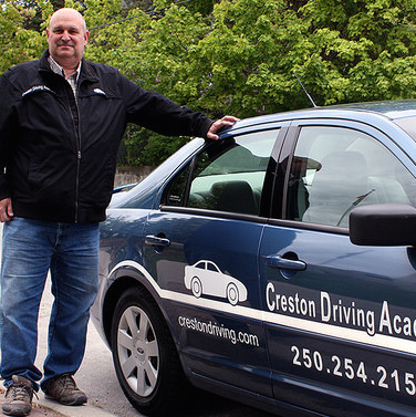 Bill Doeleman, owner and instructor at Creston Driving Academy, is standing next to one of the academy cars.