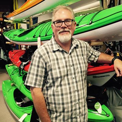 Dan Mills, standing in front of row of kayaks.
