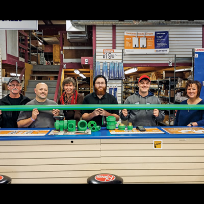 Workers at Emco in Cranbrook are lined up and holding a green pipe made by Aquatherm.