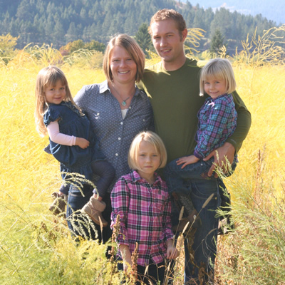 The de Vries family—Jeremy, Keely and their three daughters—stand in a field of their organic dairy farm.