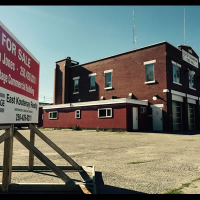 Picture of the former fire hall in Cranbrook, with a 'for sale' sign in the foreground.