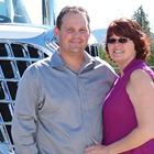 Photo of a man in a blue shirt and a woman in a pink shirt standing together in front of a semi truck.