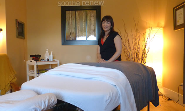 A woman with dark hair sitting at the end of a massage table.