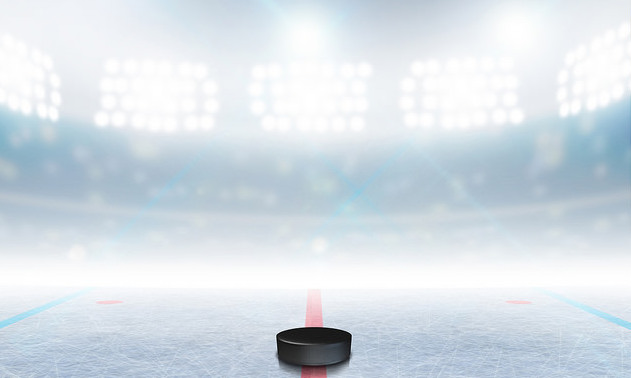 A generic ice hockey ice rink stadium with a frozen surface and a hockey puck under illuminated floodlights.