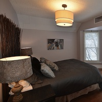 A bedroom that has been staged.  It has neutral colours on the walls, has no blinds or curtains, and no personal details on the walls.
