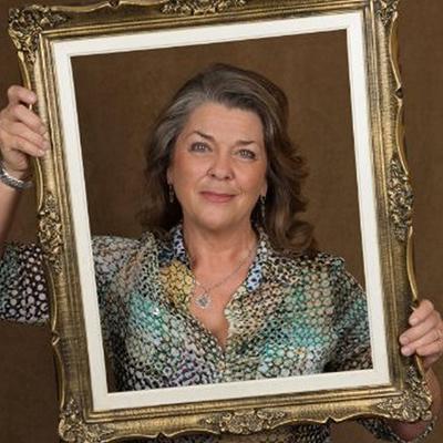 Picture of Jan Klimek, holding up decorative frame around herself.