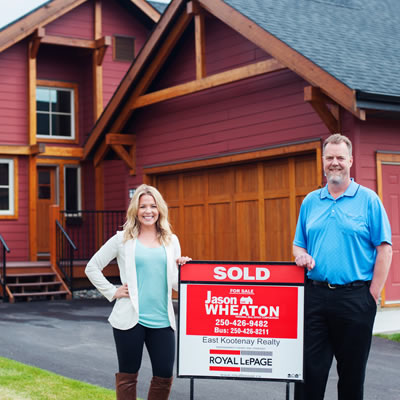 Picture of Jason Wheeldon and licensed assistant Kaytee Wheaton standing beside 'sold' sign in front of house.