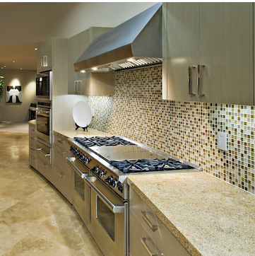 A large modern kitchen with a double stainless steel stove, and granite countertops.