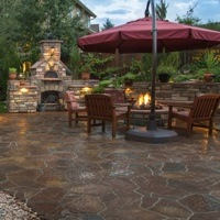 An example of a beautiful backyard that brings the indoors outside, complete with a pizza oven, fireplace, fire pit, barbecue and counter top workspace.