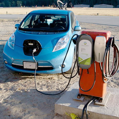 A Nissan Leaf is recharging at a unique electric car charging station at the Kettle River Museum Society in Midway. The charging station is located on the back of an old gasoline pump.