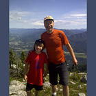 A man and young boy stand together on top of a mountain in summer