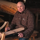 Photo of Mike Elliott working on a wooden canoe paddle with wood canoes behind