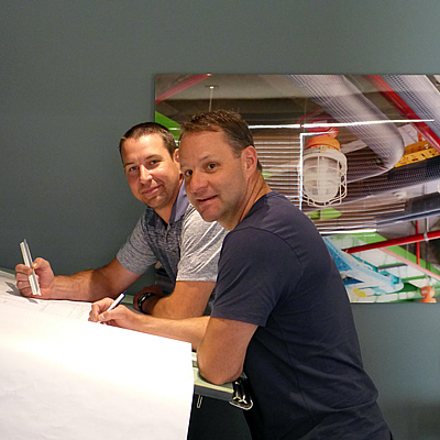 The new owners of M&K standing at a drawing board.
