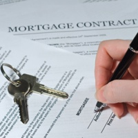 A photo of a hand signing a mortgage document.  House keys are sitting on the document.