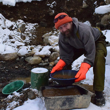 Lathem whirls the gold pan in water to remove the larger stones, leaving only a sandy sludge.