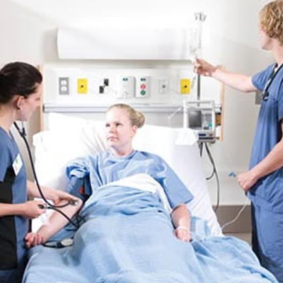Picture of patient in bed, with nurse taking blood pressure and another nurse checking IV fluid.