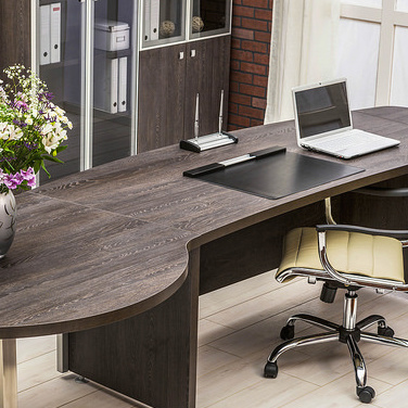 A modern office with only a laptop computer and flowers on top of the desk.