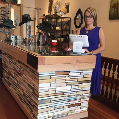Owner Zabrina Nelson of Revival Boutique stands behind a desk made of over 1,000 recycled books glued together.