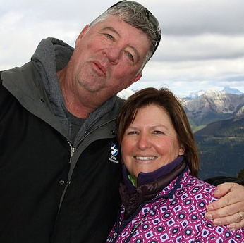 Rick and Lynn O'Neill with the snow covered Rocky Mountains in the background.