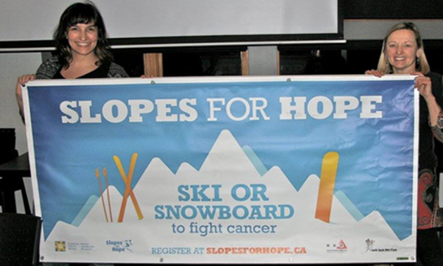 Two ladies holding up a Slopes for Hope banner