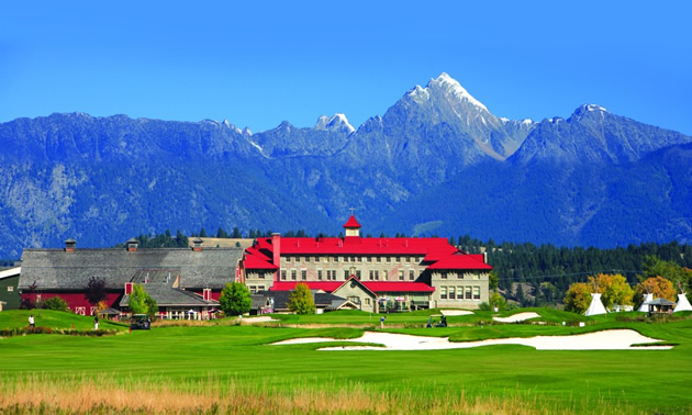 View of golf course with mountains and St. Eugene building in the far distance—building has red roof.