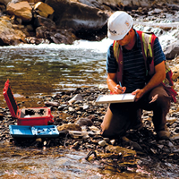 Teck worker kneeling in a creek taking samples