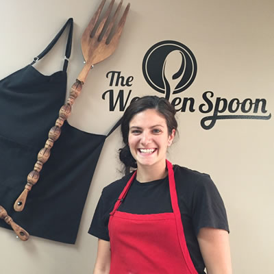 Owner and chef Kayla Sebastian of The Wooden Spoon Bistro & Bake Shop in Grand Forks is standing in front of the bistro's logo.