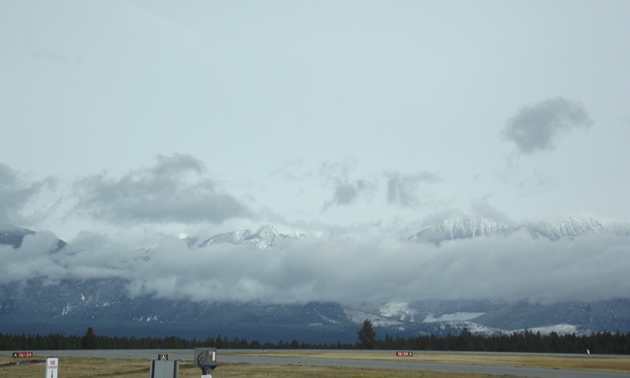 an airstrip as viewed from inside the terminal building with mountains in the distance