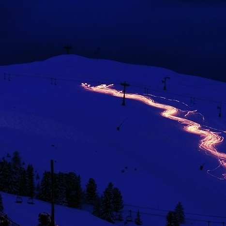 People with torches at night, going down a snowy mountain.